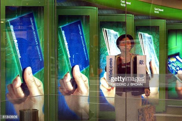 A woman stands at the entrance of a Standard Chartered Bank automaticteller machine branch 01 November 2000 in Hong Kong The Londonbased...