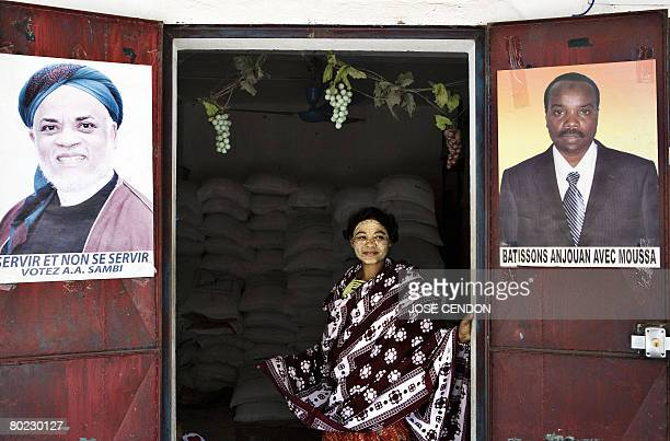 A woman stands at the threshold of a shop which shows a poster of the Comoran President Ahmed Abdallah Sambi in Mutsamudu the capital of Anjouan on...