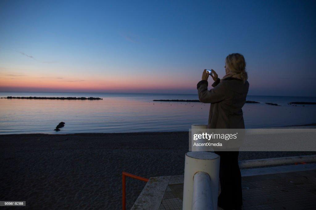 Frau steht auf Sicht in der Dämmerung und nimmt Foto mit Handy : Stock-Foto