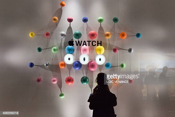 A woman stands before a window display of the Apple watch during the unveiling of the new and highly anticipated product at SaintHonore street in...