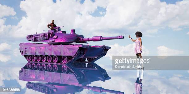 woman stands before purple tank driven by man - social inequality stock pictures, royalty-free photos & images