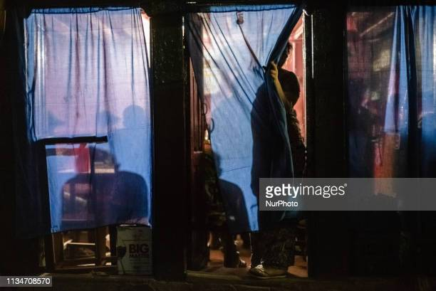 A woman stands behind a curtain at the entrance to the restaurant in Thamel district Kathmandu Nepal on April 3 2019