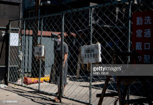 TOPSHOT A woman stands behind a fence as she waits for the delivery of goods she ordered online in the Yilanyuan residential area which is under...