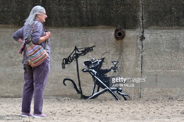 Woman stands beside a graffiti artwork of a rat drinking a cocktail, which bears the hallmarks of street artist Banksy, on a wall at North Beach in...