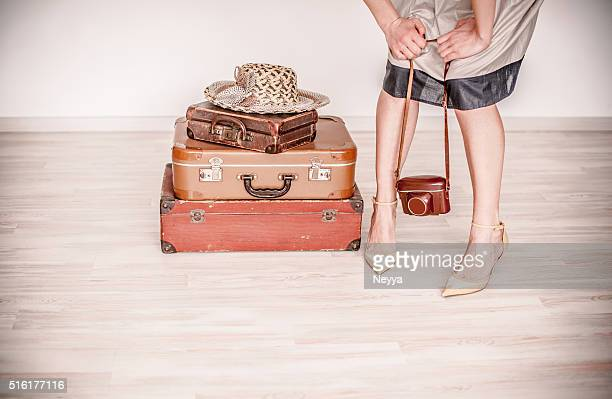 Woman stands beside a suitcase
