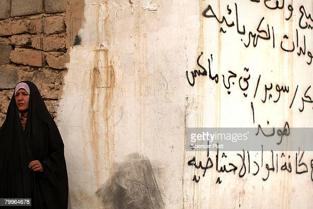 A woman stands beside Arabic graffiti on a wall February 24 2008 in Diyala Province Baquba Iraq Baquba was until recently the geographical...