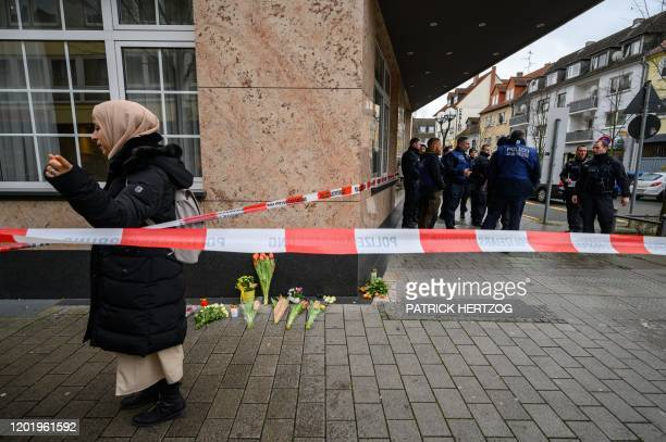 A woman stands beside candles and flowers near one of the shooting targets on February 20 at the Heumarkt in the centre of Hanau near Frankfurt am...