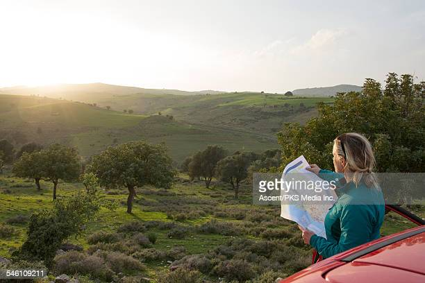 Woman stands beside car, reading road map