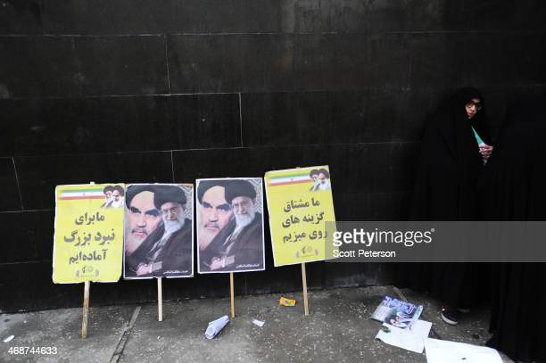 A woman stands beside posters for Ayatollahs Khomeini and Khamenei as Iranians stage a mass rally to mark the 35th anniversary of the 1979 Islamic...