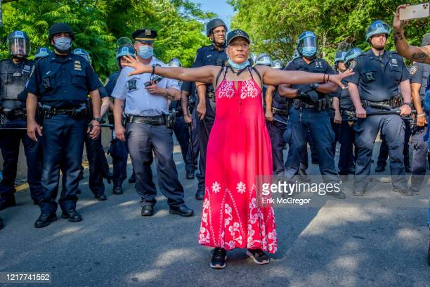 Woman stands between the poilice in riot gear and the protesters. Protesters by the thousands converged at Grand Army Plaza in Brooklyn marching down...
