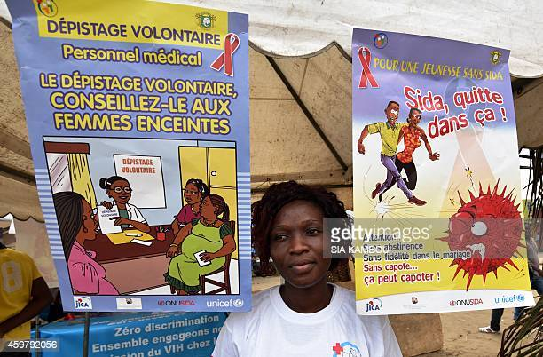 A woman stands between two posters reading how to fight against AIDS HIV on December 1 2014 at a stand in Abidjan as part of the World AIDS Day AFP...