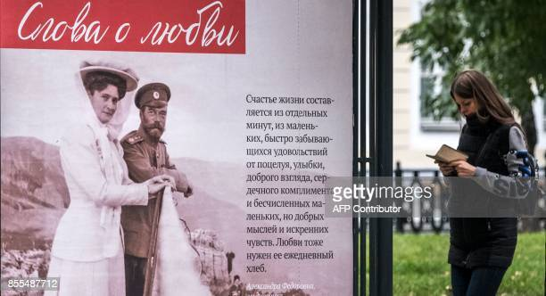 A woman stands by a billboard bearing a picture and excerpts from love letters between Tsar Nicholas II and his wife Alexandra Fyodorovna in central...