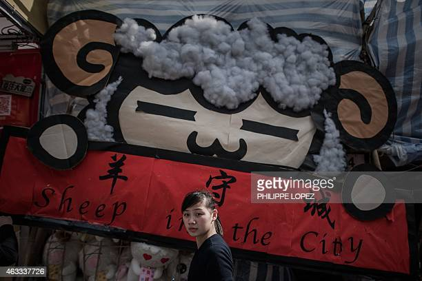 A woman stands by a billboard depicting a sheep at a Chinese New Year fair in Hong Kong on February 13 2015 The Chinese lunar new 'year of the sheep'...