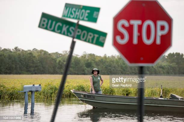 Woman stands by a boat in floodwaters from the Waccamaw River caused by Hurricane Florence on September 26, 2018 in Bucksport, South Carolina. Nearly...