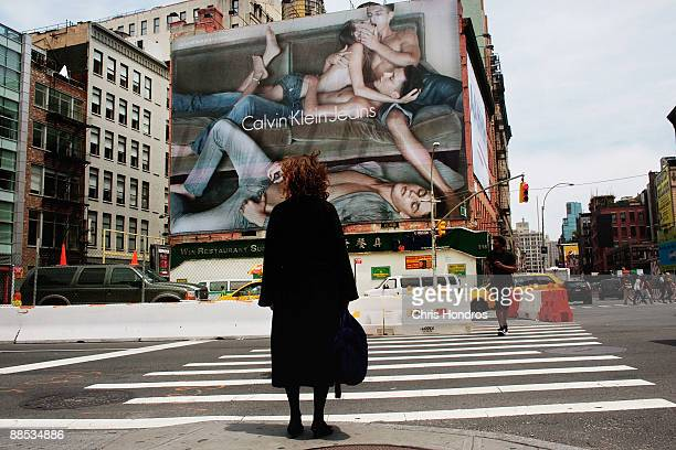 A woman stands by a crosswalk near a Calvin Klein billboard on the side of a building June 17 2009 in the SoHo neighborhood of New York City The...