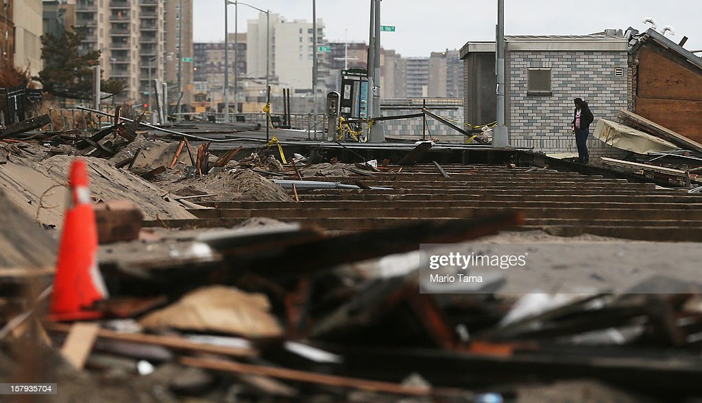 A woman stands by a destroyed section of boardwalk in the hard hit Rockaway neighborhood on December 7, 2012 in the Queens borough of New York City. Rockaway was slammed by Superstorm Sandy with many homes severely damaged from flooding.