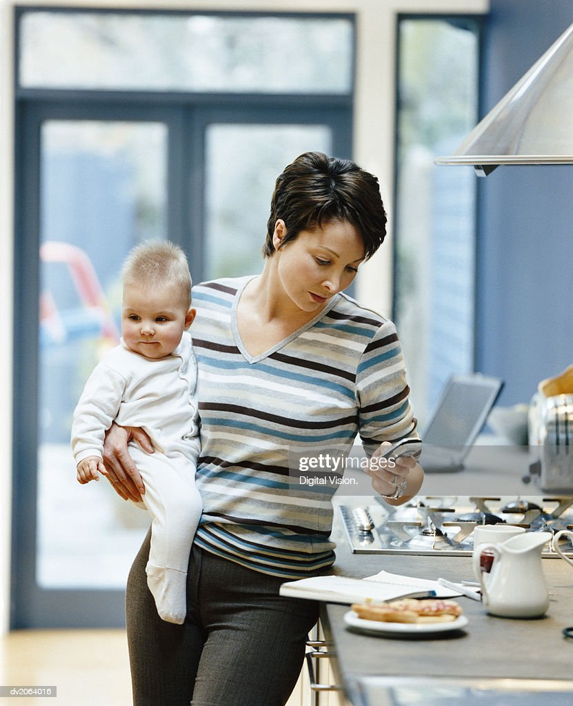 Woman Stands by a Kitchen Counter Holding Her Baby and Dialing Her Mobile Phone : Stock Photo
