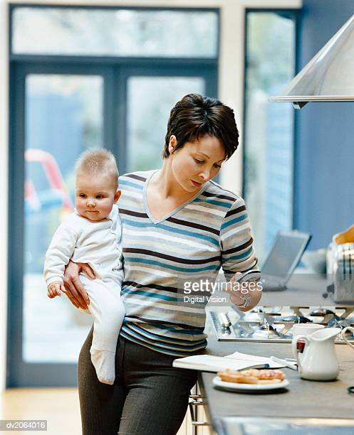 Woman Stands by a Kitchen Counter Holding Her Baby and Dialing Her Mobile Phone
