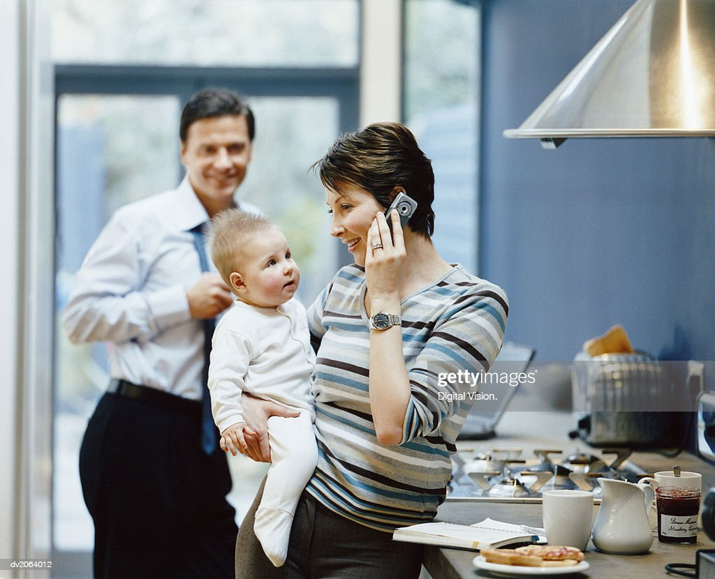 Woman Stands by a Kitchen Counter Holding Her Baby and Talking on Her Mobile, Father in the Background : Stock Photo