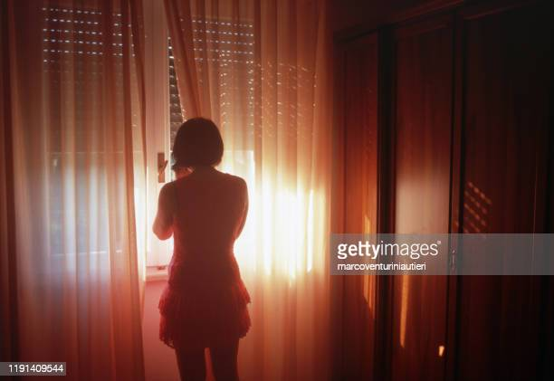 woman stands by a window with a beautifully lit curtain - marcoventuriniautieri stock pictures, royalty-free photos & images