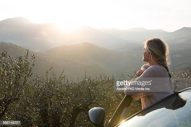 Woman stands by car door, looks to sunrise, hills