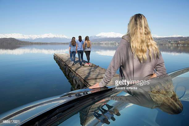 Woman stands by car, watches girls walk down pier