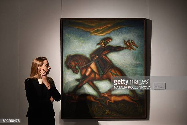A woman stands by the painting 'The Hunter' by Dmitri Stelletsky during a preview of Sotheby's forthcoming Russian Pictures Including the BarGera...