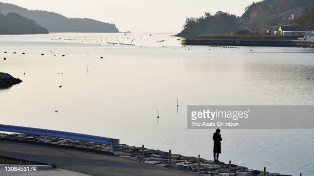 Woman stands by the sea on the 10th anniversary of the Great East Japan Earthquake and following tsunami on March 11, 2021 in Ishinomaki, Miyagi,...