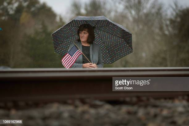 A woman stands by the tracks along a rural road as she waits for the train carrying the casket of former President George HW Bush to his final...