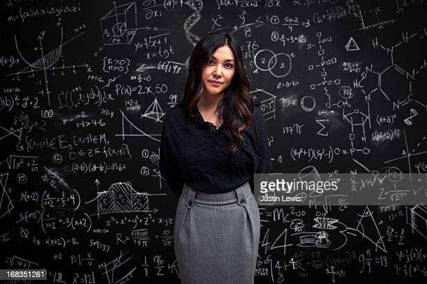 woman stands calm in front of math chalkboard - wisdom stock pictures, royalty-free photos & images