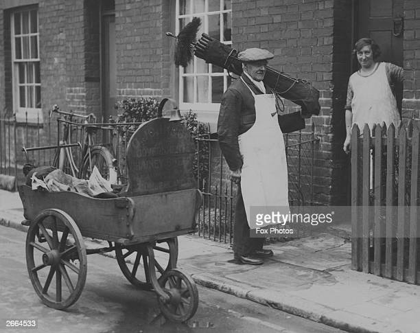 A woman stands chatting to a chimney sweep on her doorstep