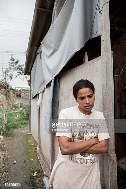 A woman stands for a photograph in the Dilma Rousseff favela of Rio de Janeiro Brazil on Monday July 6 2015 As the fastest inflation in more than a...