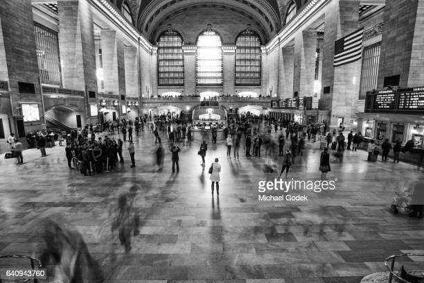 a woman stands front and center in grand central station while the motion blur of crowds move past her on either side - grand central station manhattan - fotografias e filmes do acervo