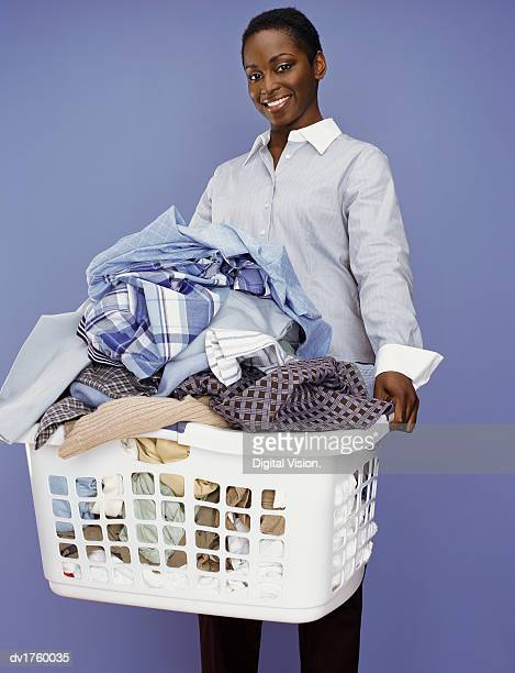 Woman Stands Holding a Washing Basket Full of Laundry