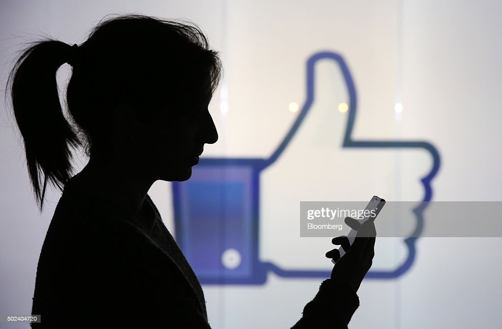 A woman stands holding her smartphone whilst framed against a wall bearing Facebook Inc.s 'Thumbs Up' symbol in this arranged photograph in London, U.K., on Wednesday, Dec. 23, 2015. Facebook Inc.s WhatsApp messaging service, with more than 100 million local users, is the most-used app in Brazil, according to an Ibope poll published on Dec. 15. Photographer: Chris Ratcliffe/Bloomberg via Getty Images