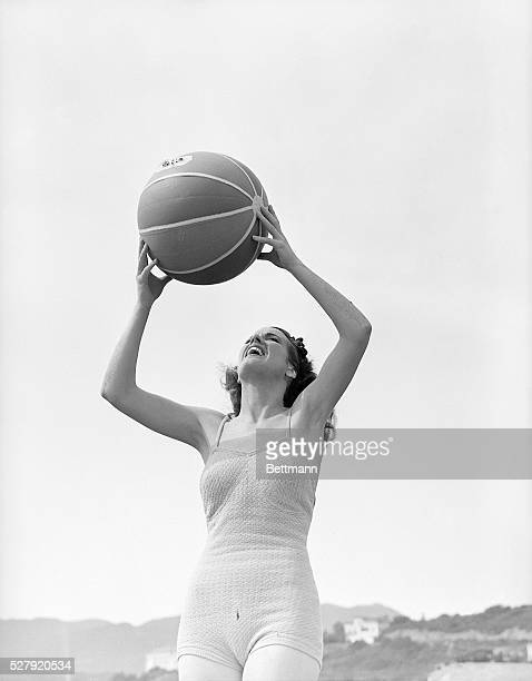 A woman stands in a bathing suit holding a beach ball above her head Undated photograph circa 1950's