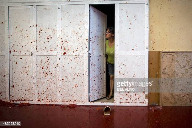 A woman stands in a doorway covered in tomato pulp during the annual 'tomatina' festivities in the village of Bunol near Valencia on August 26 2015...