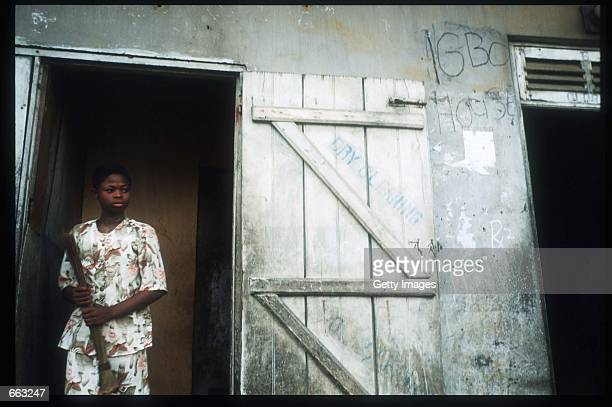 A woman stands in a doorway December 15 1999 in the Ajegunle area of Lagos Nigeria Signs painted on the fronts of the houses indicate that the...