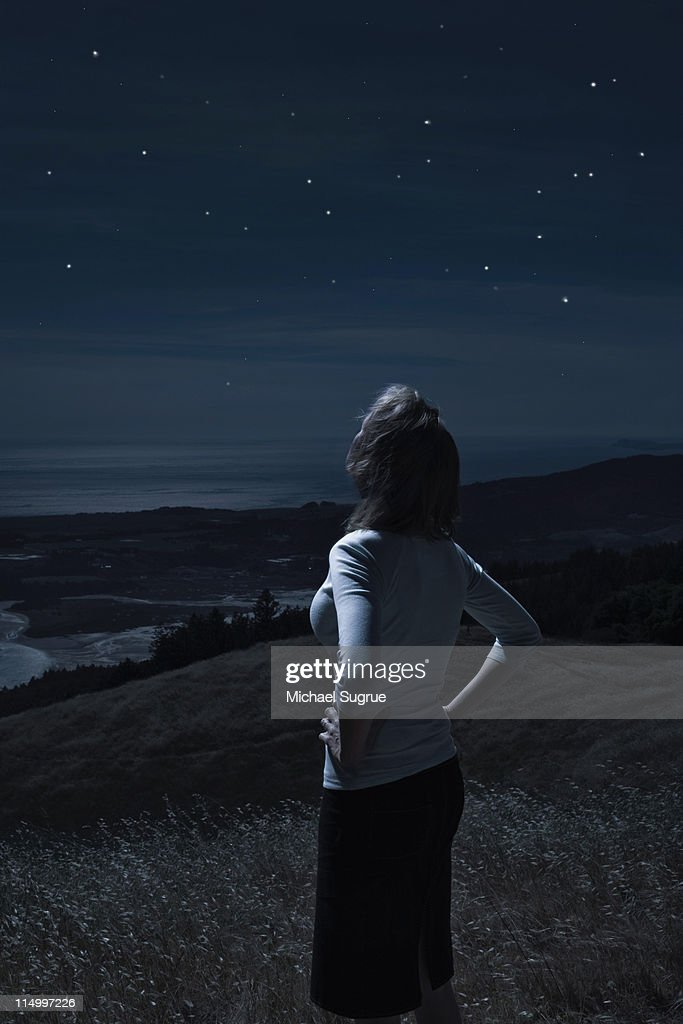A woman stands in a field at night, staring up.