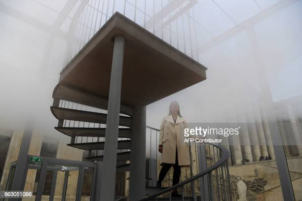 A woman stands in a glass cube containing an olfactory cloud Le Nuage Parfumé or OSNI 1 launched by Cartier and displayed outside the Palais de Tokyo...