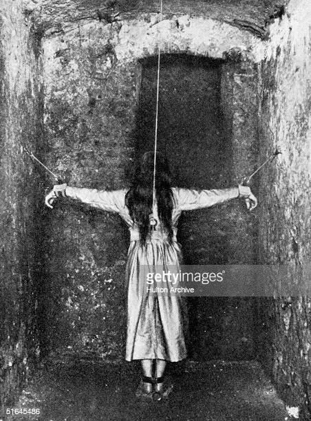 A woman stands in a narrow cell her arms affixed to the wall in the attitude of the crucifixion circa 1890 She is undergoing treatment for mental...