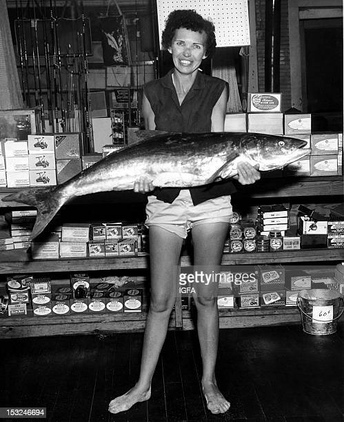 A woman stands in a shop holding a 44 pound cobia caught on 20 pound line in Melbourne Beach Florida on June 4 1959