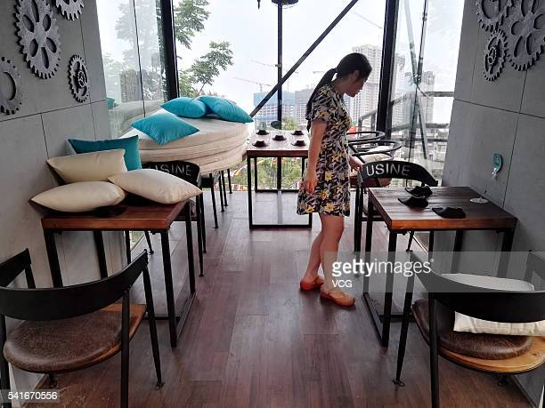 Woman stands in a small bar built in slanted shipping container on June 19 2016 in Chengdu Sichuan province of China The bar is elevated from the...