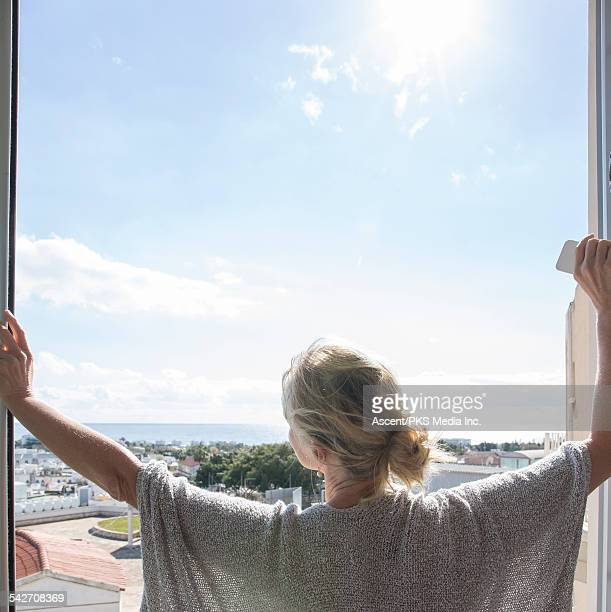 Woman stands in doorway, looks past village to sea
