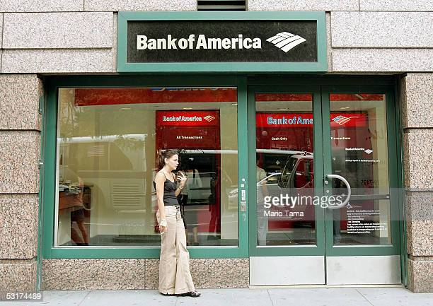 A woman stands in front of a Bank of America branch June 30 2005 in New York City Bank of America Corp the second largest US bank agreed to buy MBNA...