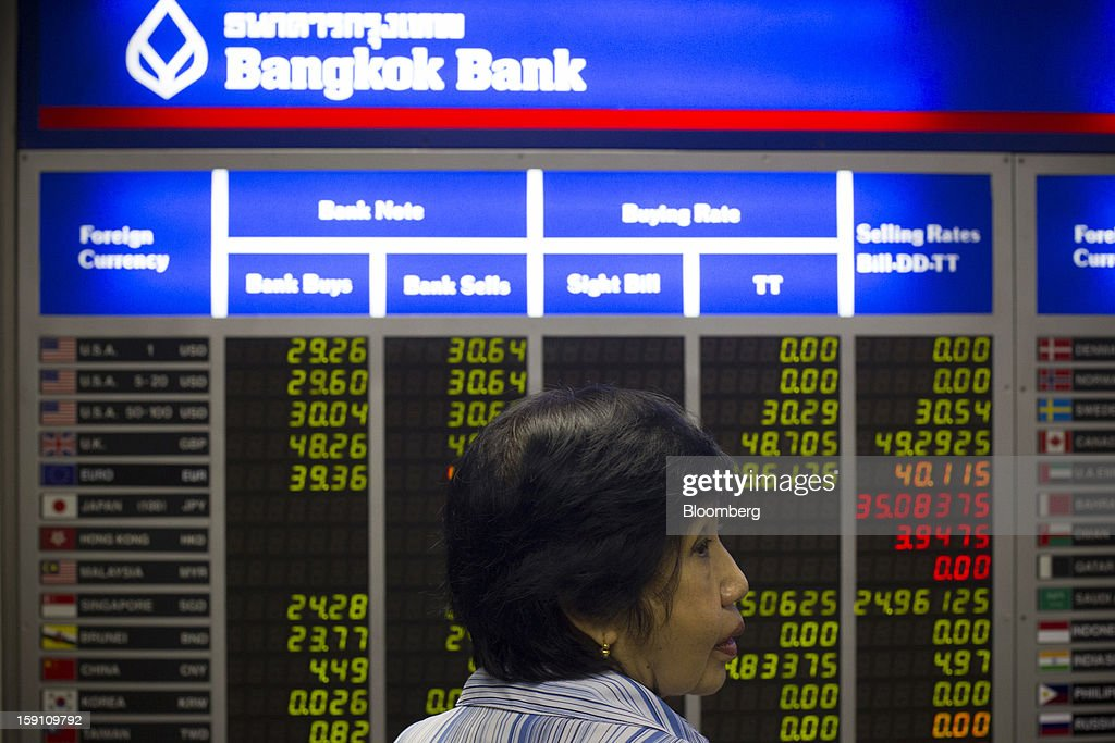 A woman stands in front of a board displaying foreign exchange rates at the Bangkok Bank Pcl. headquarters in Bangkok, Thailand, on Tuesday, Jan. 8, 2013. Thailand's economy may have expanded 5.7 percent in 2012 and will grow 5 percent in 2013, the finance ministry said on Dec. 26. Photographer: Brent Lewin/Bloomberg via Getty Images