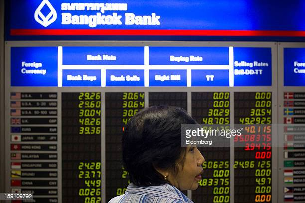 A Woman Stands In Front Of Board Displaying Foreign Exchange Rates At The Bangkok Bank
