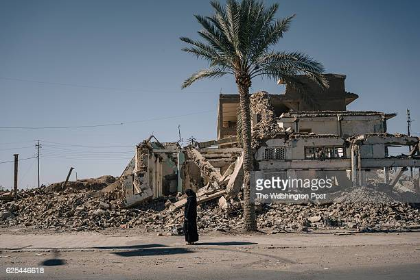 A woman stands in front of a destroyed building in Tikrit