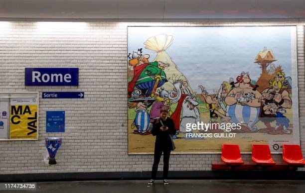 A woman stands in front of a drawing especially designed to commemorate the 60th anniversary of France's famous comic characters Asterix and Obelix...