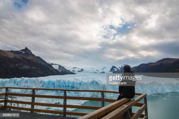 Woman stands in front of a glacier